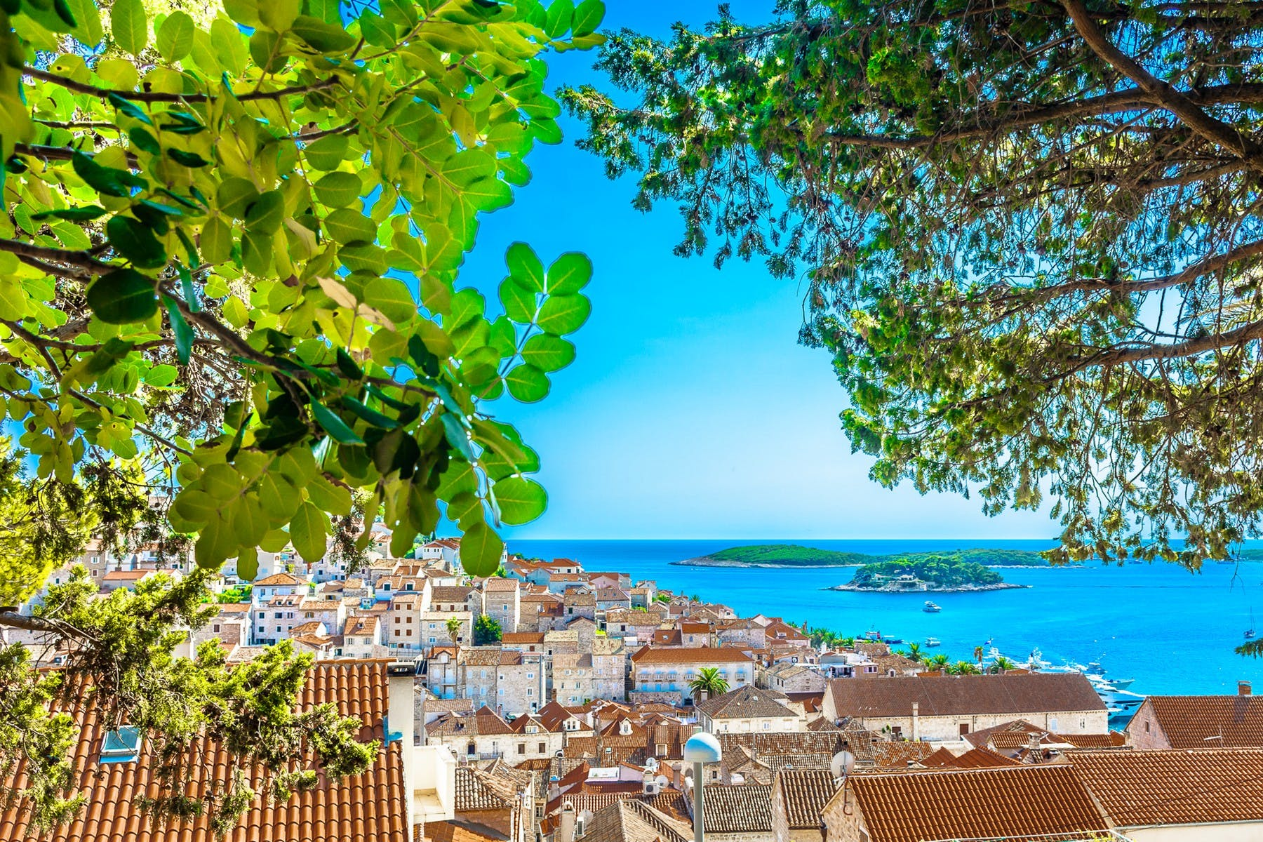View of red roofs and clear blue sea of city of Hvar