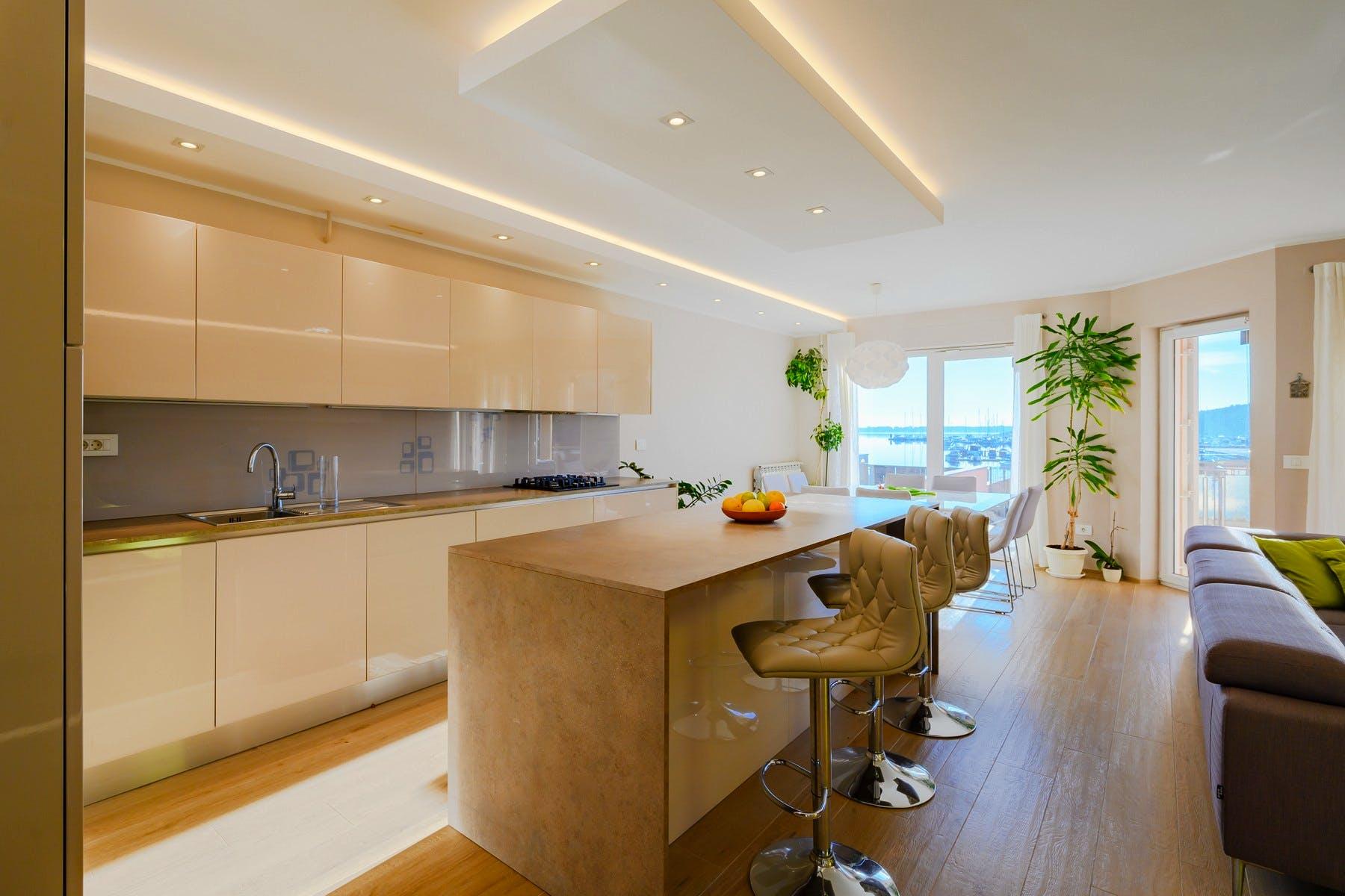 Velika kuhinja s otokom i blagovaonskim stolom za osam osoba