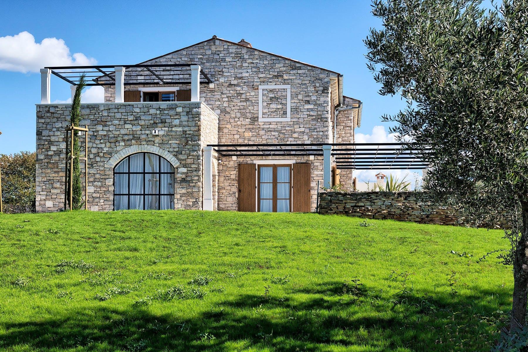 Rustikalna vila s velikim staklenim prozorima kroz koje se pruža pogled od kojeg zastaje dah