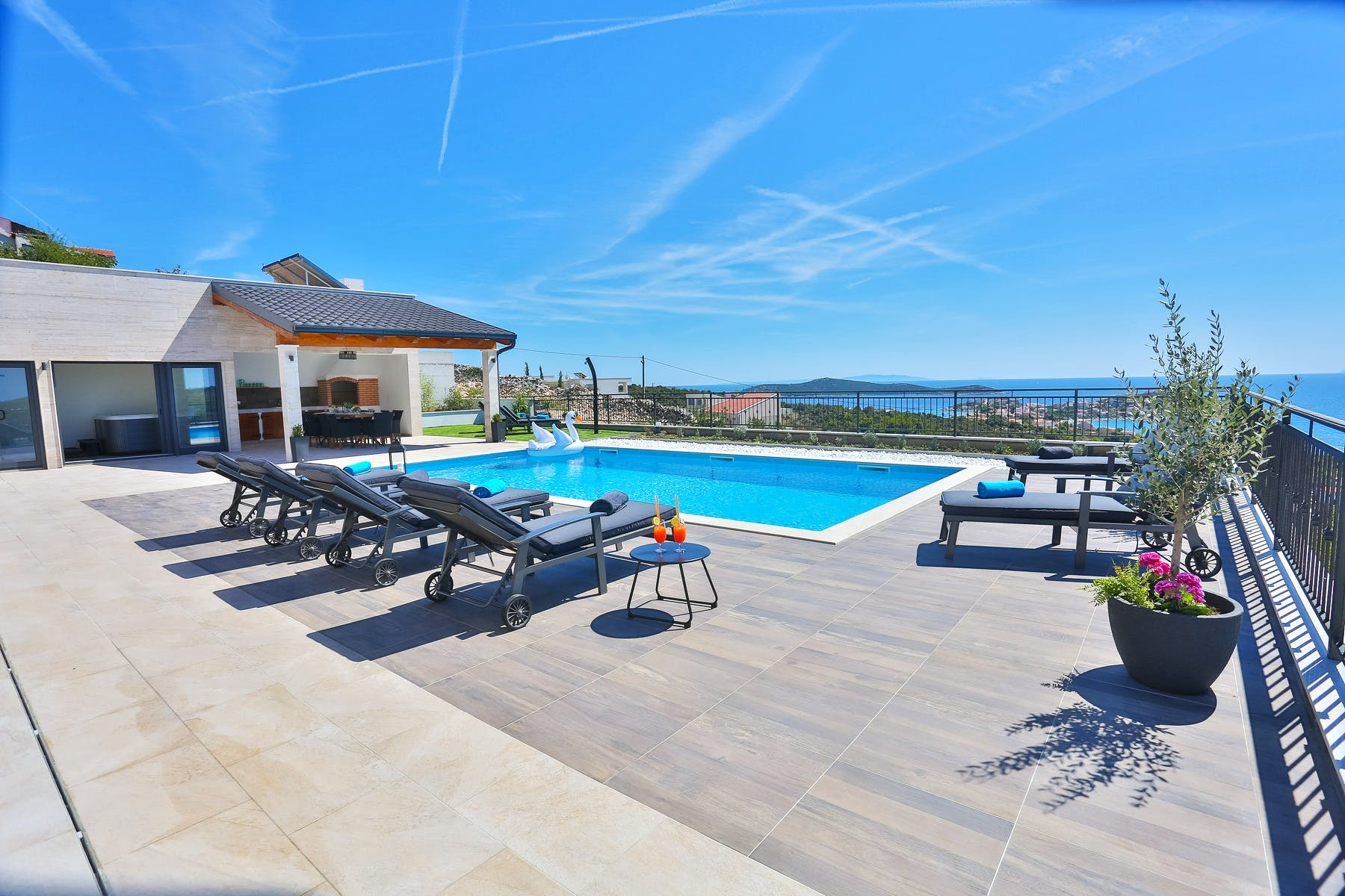 Spacious terrace with swimming pool, sun deck and sea view