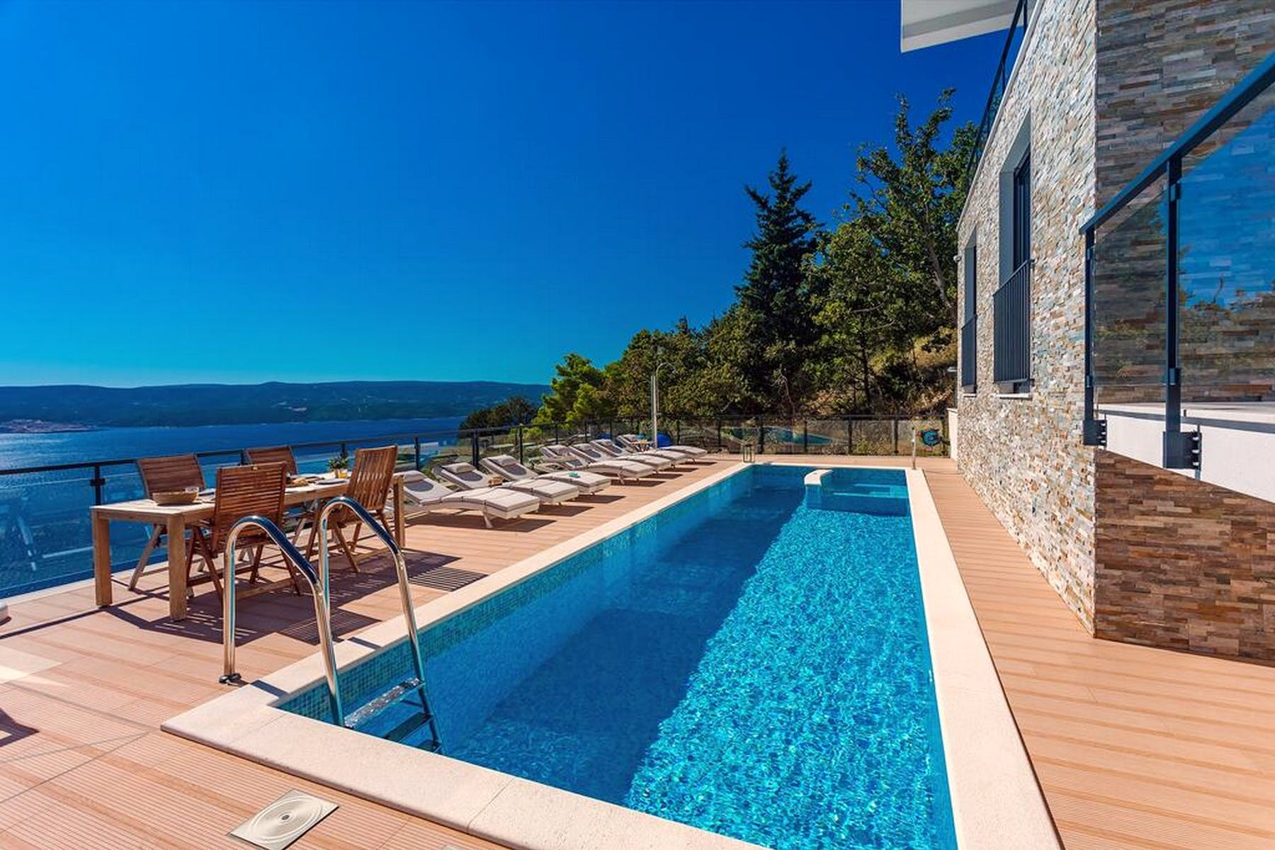 Spacious swimming pool and sundeck overlooking the sea