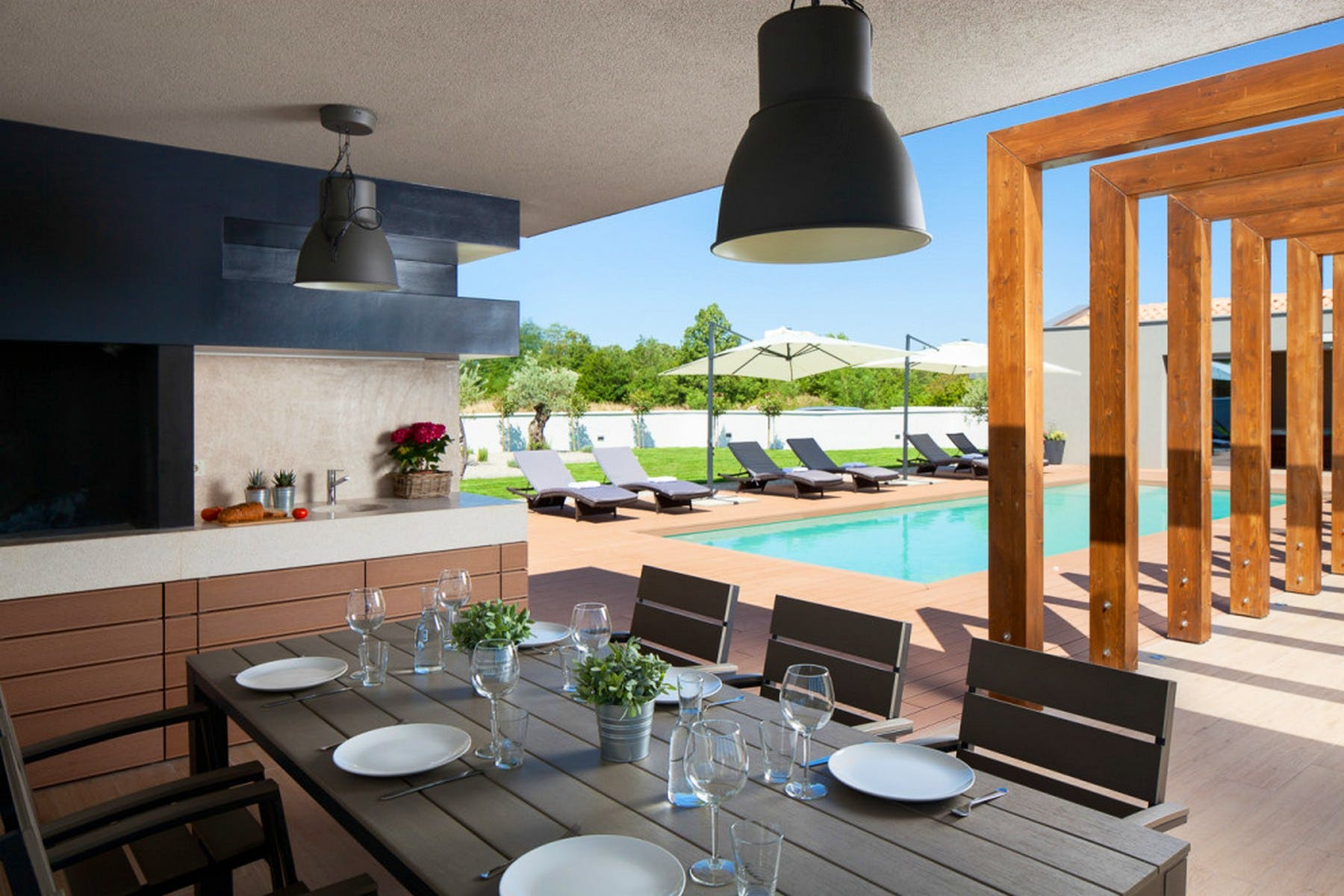 Summer kitchen and outside dining area with view of the pool